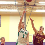 Pine City's Nick Hansmann shoots in front of Duluth Denfeld's Aldrick Hopkins in the Wood City Classic