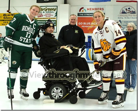 Matt Olson poses with UMD's Sydney Brodt and Bemidji State's Emma Terres after Monday night's ceremonial puck drop prior to the Hockey HOF game at Isanti Arena.